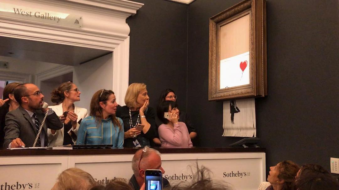 """Banksy posted a photo on Instagram of the shredded work dangling from the bottom of the frame with the title """"Going, going, gone … """""""