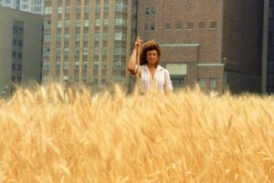 Wheatfield – A Confrontation: Battery Park Landfill, Downtown Manhattan – With Artist in the field, 1982, by Agnes Denes